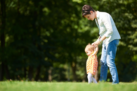 toddler walking: happy mother and baby child in park making first steps .  Walking and hugging.
