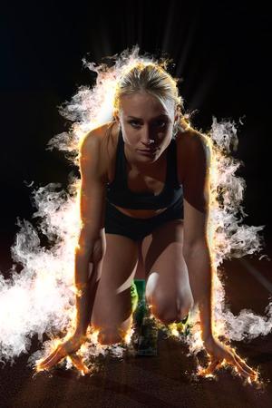 ontwerp met vuur, rook en Burm van de vrouw sprinter startblokken verlaten op de atletiekbaan. Zijaanzicht. exploderende start Stockfoto