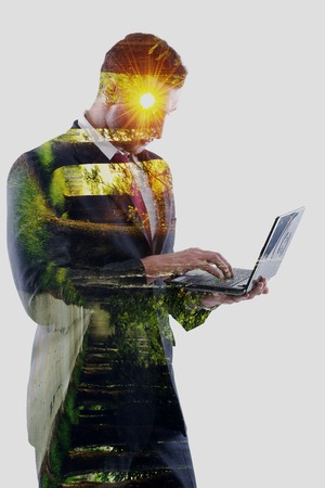 double exposure of business man who working on laptop computer  and alley with trees and sunrise photo