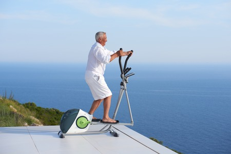 modern home: healthy senior man working out on gym treadmill machine at modern home terace with ocean view