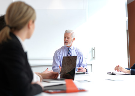 senior adults: business people group on meeting at modern bright office indoors. Senior  businessman as leader in discussion.