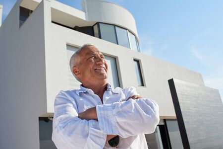 one person: senior man in front of luxury modern home villa Stock Photo