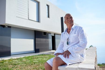 garden key: senior man in front of luxury modern home villa Stock Photo