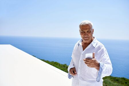 old technology: senior man using smart phone outdoor with ocean view background