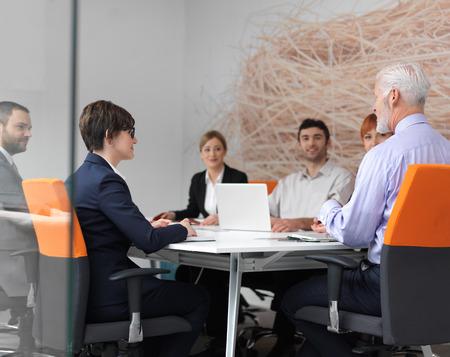 lider: grupo de personas de negocios sobre la reunión en la oficina moderna brillante en el interior. Hombre de negocios mayor como líder en la discusión.
