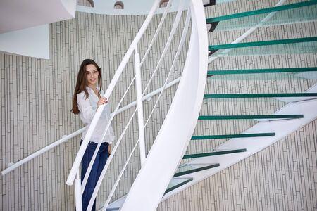 personas sentadas: mujer joven que recorre en las escaleras de caracol en casa moderna en el interior