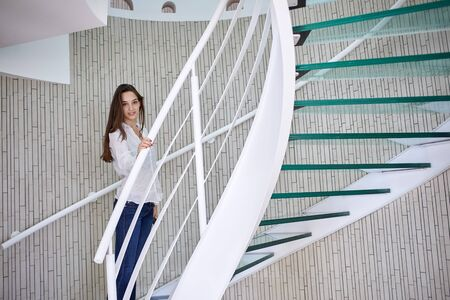 sitting people: young woman walking on spiral stairs in modern home indoors