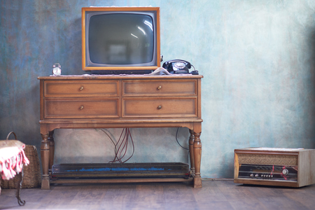 old time: Vintage retro look living room detail. Television, telephone and clock on wooden old table Stock Photo