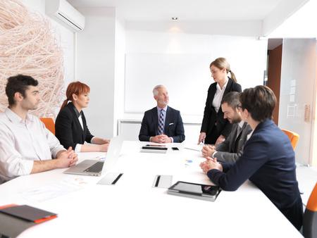 reunion de trabajo: grupo de personas de negocios sobre la reunión en la oficina moderna brillante en el interior. Hombre de negocios mayor como líder en la discusión.