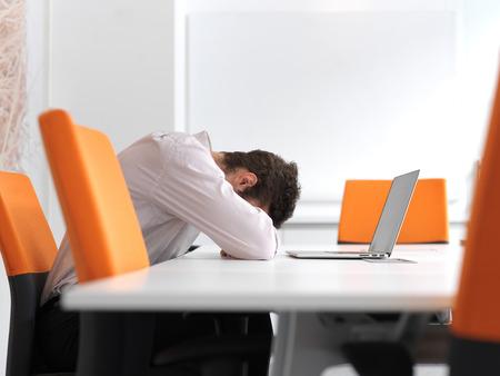 Gefrustreerde jonge zakenman hebben van stress problemen. Zit alleen op het kantoor van vergaderruimte en werken op de laptop berekenen.