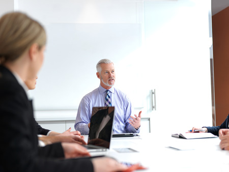 office women: business people group on meeting at modern bright office indoors. Senior  businessman as leader in discussion.