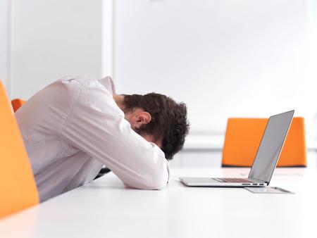 dolor de cabeza: Frustrado hombre de negocios joven tiene problemas de estrés. Sentado solo en la oficina sala de reuniones y trabajando en calcular portátil. Foto de archivo