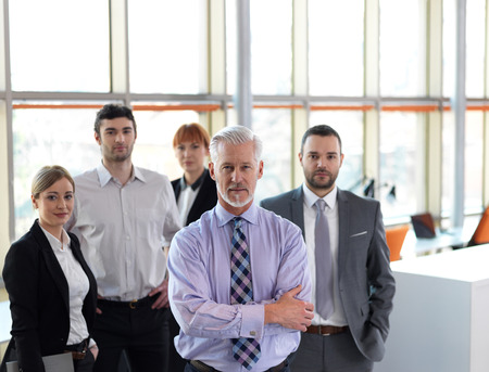 smiling businessman: senior businessman with his team at office. business people group