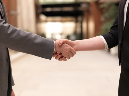 businessmen shaking hands: business partners concept with businessman and businesswoman handshake at modern office indoors