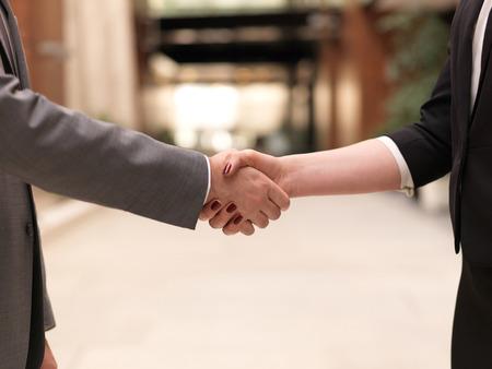zakelijke partners concept met zakenman en zakenvrouw handdruk op moderne kantoor binnenshuis Stockfoto