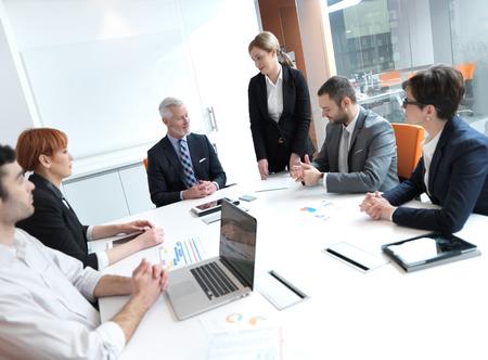 bedrijfsleven groep mensen op vergadering op moderne lichte kantoor binnen. Senior zaken als leider in discussie. Stockfoto