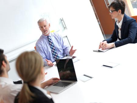 personas trabajando oficina: grupo de personas de negocios sobre la reuni�n en la oficina moderna brillante en el interior. Hombre de negocios mayor como l�der en la discusi�n.