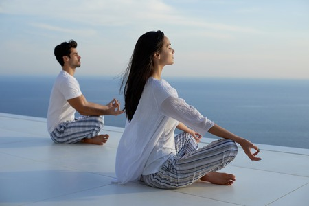young couple practicing yoga at sunset in modern home terace with ocean and sunset in background Archivio Fotografico