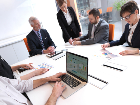 computers office: business people group on meeting at modern bright office indoors. Senior  businessman as leader in discussion.