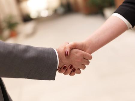saludo de manos: socios de negocios concepto con el hombre de negocios y apretón de manos de negocios en la oficina moderna interior Foto de archivo
