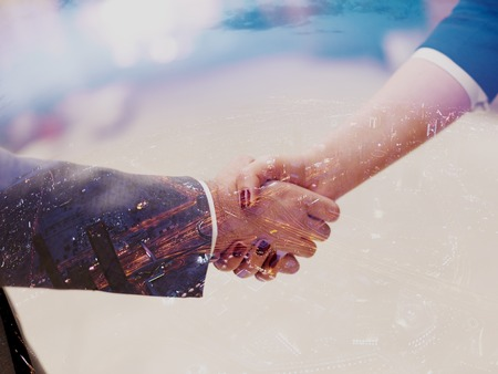Double exposure design. Business partners concept with businessman and businesswoman handshake at modern office indoors Stock Photo