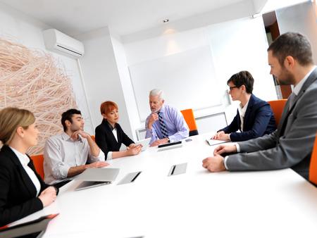 ejecutivo en oficina: grupo de personas de negocios sobre la reuni�n en la oficina moderna brillante en el interior. Hombre de negocios mayor como l�der en la discusi�n.