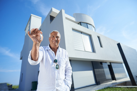 front house: senior man in front of luxury modern home villa Stock Photo
