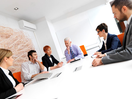 business people meeting: business people group on meeting at modern bright office indoors. Senior  businessman as leader in discussion.