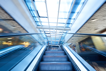 view of a staircase in a shop: Shopping mall center escalators. Zoom blur movement. Stock Photo