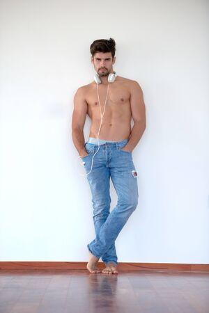 desnudo masculino: apuesto joven escuchando música en los auriculares en el hogar moderno sobre la pared blanca y de pie en las manos