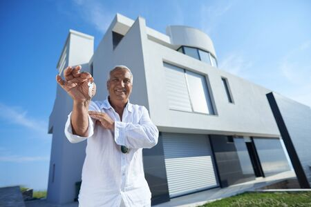 rich people: senior man in front of luxury modern home villa Stock Photo