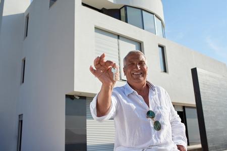 zakelijk: senior man in de voorkant van luxe moderne huis villa Stockfoto