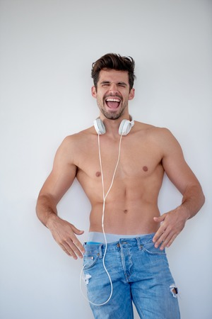 male model: handsome young man listening music on headphones at modern home over  white wall and standing on hands