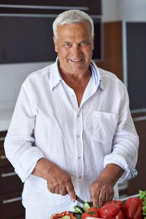 hombre cocinando: Hombre mayor hermoso que cocina en casa preparando la ensalada en la cocina. Foto de archivo