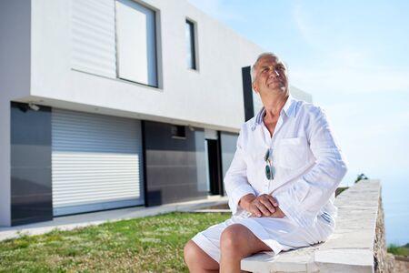 modern home: senior man in front of luxury modern home villa Stock Photo