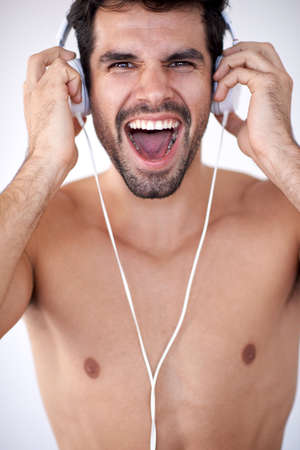 male hand: handsome young man listening music on headphones at modern home over  white wall and standing on hands
