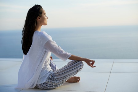 giovane donna pratica yoga meditaion sul tramonto con vista mare in background