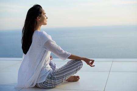 junge Frau, die Yoga praktizieren meditaion auf Sonnenuntergang mit Blick aufs Meer im Hintergrund
