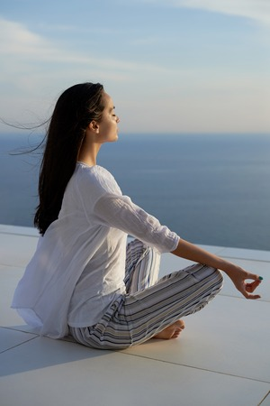 meditaion: young woman practice yoga meditaion on sunset with ocean view in background