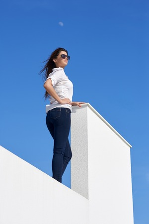 background person: relaxed young beautiful woman in front of luxury modern home villa  on balcony on sunny day