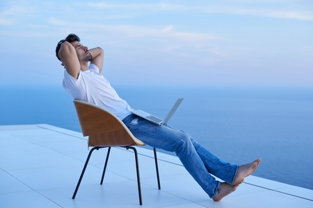 man working computer: handsome young man relaxing and working on laptop computer at home balcony while looking sunset