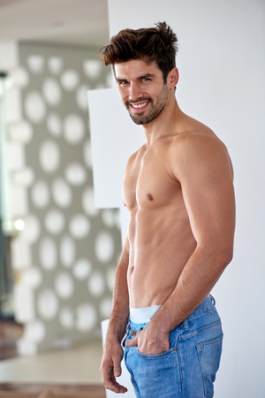 Hot house: shirtless handsome young man in jeans posing at modern home indoors Stock Photo