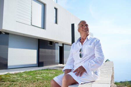 happy home: senior man in front of luxury modern home villa Stock Photo