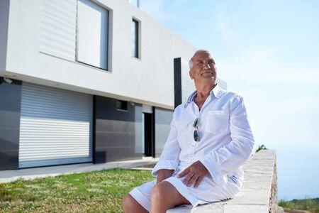 retirement happy man: senior man in front of luxury modern home villa Stock Photo