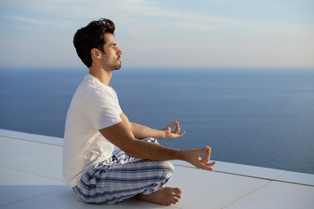 men health: handsome young man practicing yoga on in modern home terace with ocean and sunset in background Stock Photo