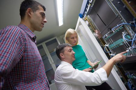 servers: business people group, network engeneers working in network server room on tablet computer