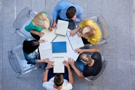group meeting: top view,  group of students together  at school table working homework and have fun