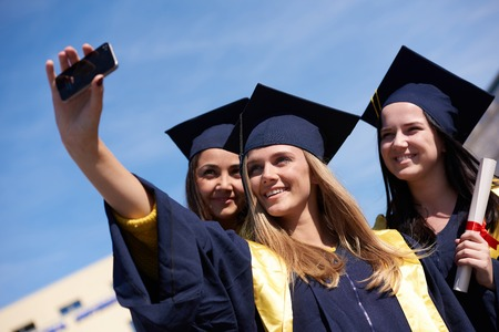 capturing: Capturing a happy moment.Students group  college graduates in graduation gowns  and making selfie photo