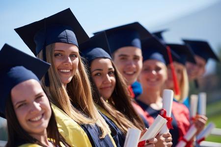 grupo de jóvenes estudiantes de pie en frente del edificio de la universidad el día de graduación graduados Foto de archivo