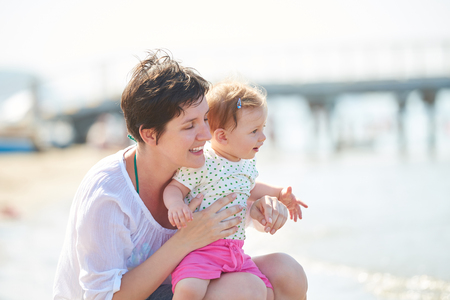 happy mom: happy mom and baby on beach  have fun while learning to walk and  make first steps